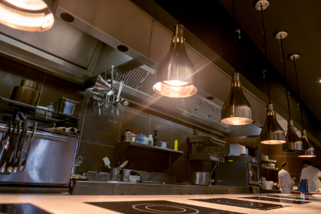 Heat lamps hanging over a clean kitchen line